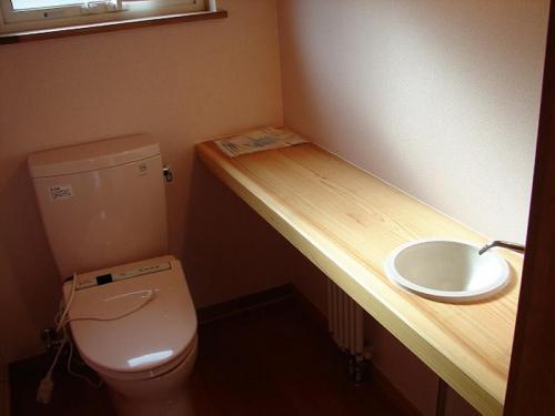 二階のトイレには無垢の杉の板をそのまま使いくり貫いた手洗いカウンター。無垢の柔らかさと優しさが感じられます。