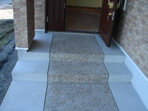 玄関アプローチには天然の川砂利を使った洗い出し〔乾く前に表面のモルタルを洗い落とす工法〕で、やわらかい風合いを出してみました。