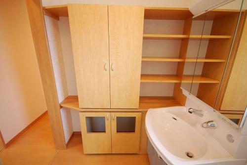 浴室に隣接する洗面脱衣室。洗面化粧台の隣にはタオルや着替えも収納できる手作りの棚。下には使い終わったタオルなどをドアを開けずに入れることのできるように四角い穴が↑